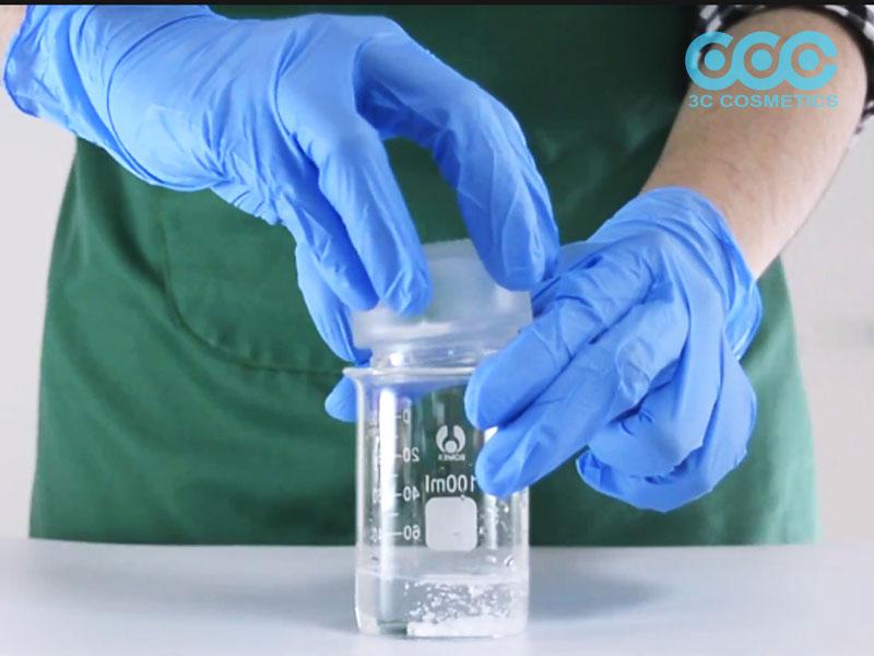 Cho nước, Sodium Benzoate, Sodium Choloride vào cốc thủy tinh và khuấy tan